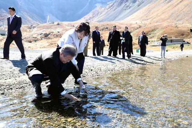 Bà Kim Jung-sook tiến đền chỗ ông Moon Jae-in để chỉ cho ông cách lấy nước từ hồ Chonji vào chai (Ảnh: Reuters)