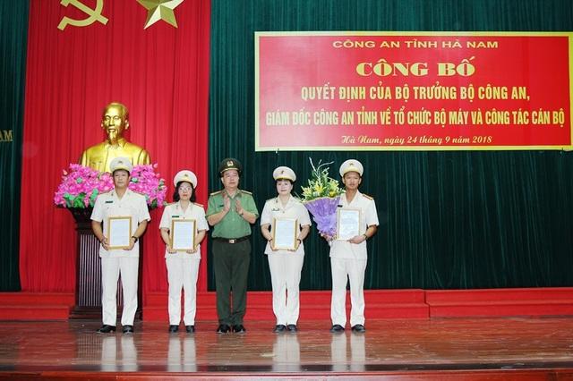 Đại tá Nguyễn Đại tá Nguyễn Văn Trung, Giám đốc Công an tỉnh trao quyết định và tặng hoa chúc mừng các Trưởng phòng, phó trưởng phòng.