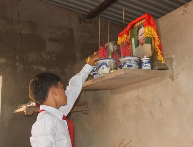 Em Quang đứng trước bàn thờ mẹ hứa sẽ chăm chỉ học tập