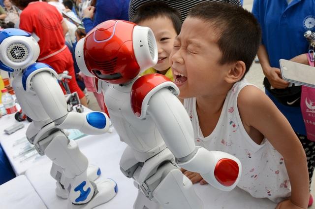 Trẻ em chơi đùa với robot tại một triển lãm ởTrung Quốc.
