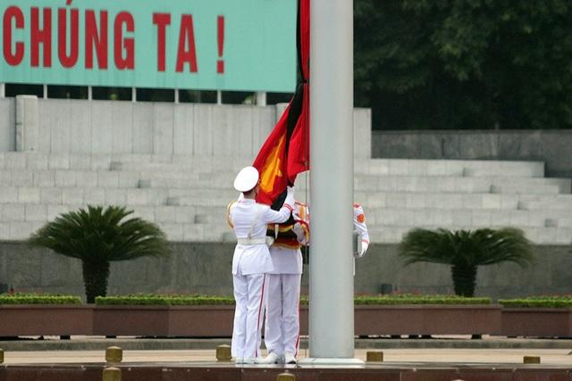 Ba chiến sĩ tiến về cột cờ thực hiện nghi thức treo cờ rủ.
