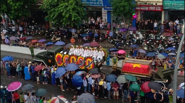 Người dân Ninh Bình đội mưa đứng kín hai bên đường đón đoàn xe chở linh cữu Chủ tịch nước. (Ảnh: Nguyệt Ánh)