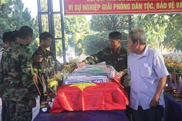 Lực lượng chức năng chỉnh trang lại cờ Tổ quốc trên các hài cốt.