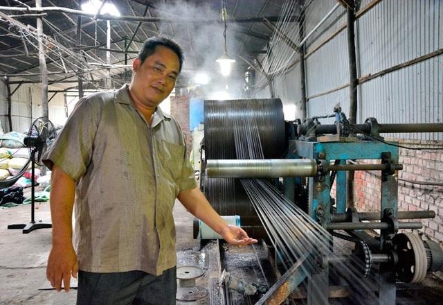 Anh Kiệt đang theo dõi quy trình sản xuất chỉ nhựa tại cơ sở. Ảnh: NQ.
