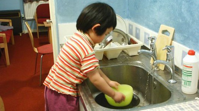Hướng dẫn trẻ làm việc nhà là tốt song không được bắt trẻ làm việc quá sức, ảnh hưởng tới sức khỏe và thời gian học tập, vui chơi của trẻ. (Ảnh minh hoạ)