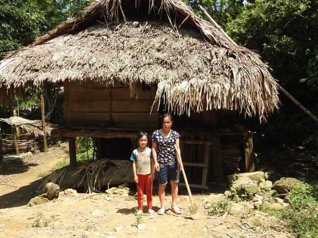 Hai mẹ con chị Xa Thị Mang đang ở trong căn nhà tạm bợ thưng bằng gỗ, mái lợp tranh
