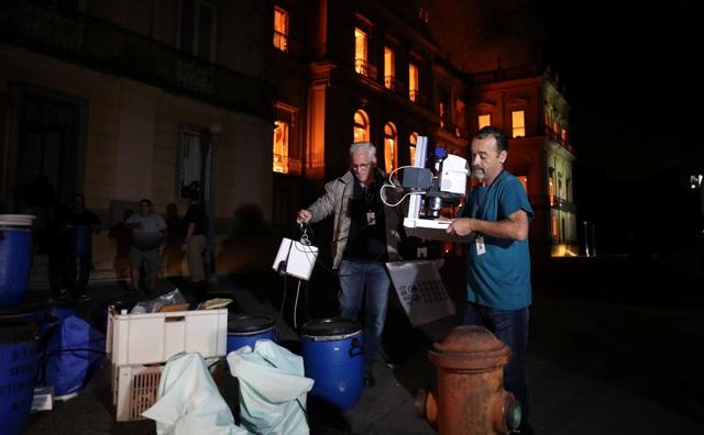 Mọi người khẩn trương sơ tán các hiện vật ra khỏi tòa nhà đang bốc cháy.