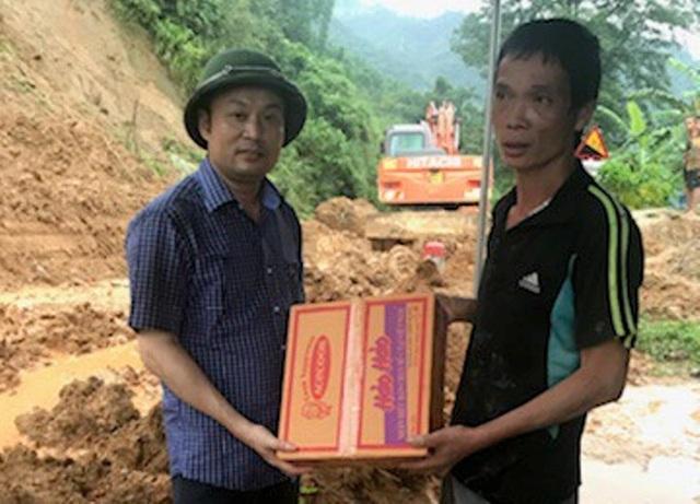 Ông Cao Văn Cường, Chủ tịch UBND huyện Mường Lát (người đội mũ cối) trao hàng cứu trợ cho bà con xã Trung Lý