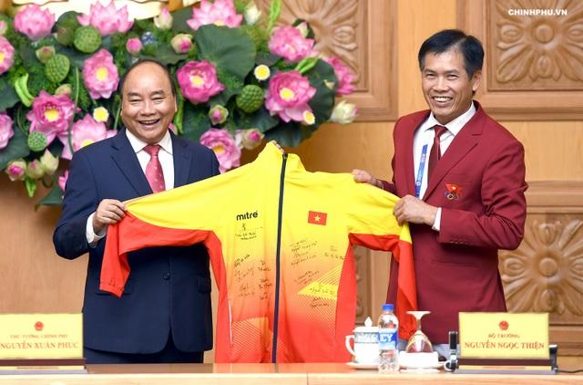 Thủ tướng nhận quà kỷ niệm là chiếc áo đấu có chữ ký của các cầu thủ đội Olympic Việt Nam