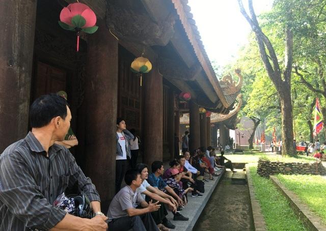 Nhiều người dân, du khách ngồi nghỉ ngơi bên hiên của Chính điện Lam Kinh.