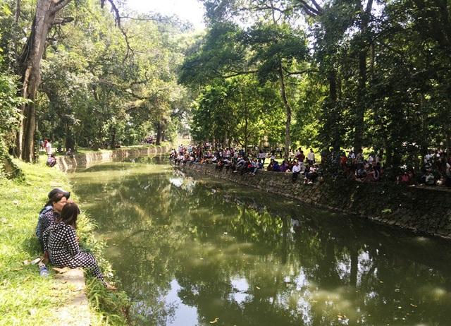 Người dân và du khách ngồi nghỉ, tận hưởng cảm giác mát mẻ bên dòng sông Ngọc.