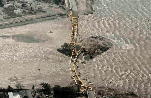 Một cây cầu bị sóng thần cuốn phăng (Ảnh: Reuters)
