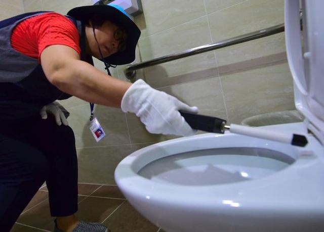 Một nhân viên dùng thiết bị dò camera để tìm những thiết bị quay lén trong nhà vệ sinh công cộng tại Hàn Quốc (Ảnh: AFP)