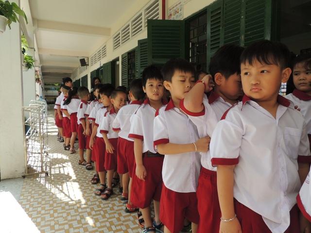 Học sinh trong một lớp của lớp 1 tại Trường tiểu học Hồng Hà, Bình Thạnh, TPHCM xếp hàng dài dằng dặc tập đi vệ sinh, uống nước.