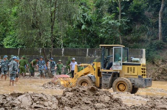 Máy xúc được huy động đến để xúc lớp bùn đất phủ ở sân trường Nà Ớt - Sơn La lên tới gần 1m.