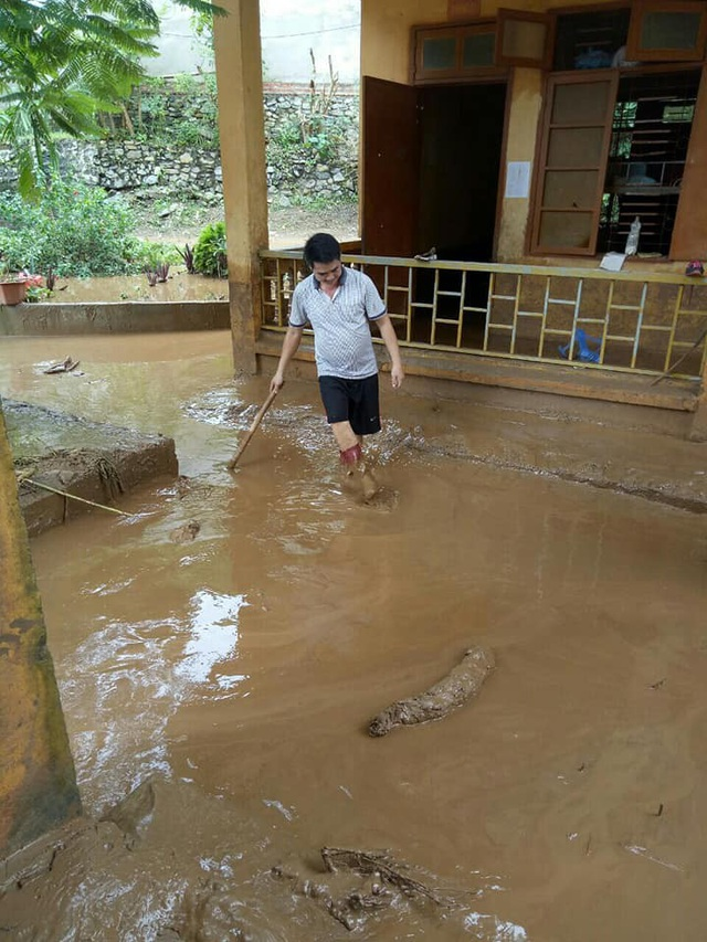 Giáo viên Trường THCS Tà Hộc vất vả quét dọn từng khối bùn đất ngập ở sân trường