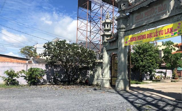 Cổng chùa ven quốc lộ 1, nơi xảy ra vụ việc tài xế taxi bỏ lại hành khách cùng người thân đã tử vong xuống đường.