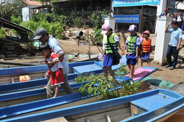 Các em học sinh trường tiểu học B Vĩnh Hội Đông (huyện An Phú, tỉnh An Giang) được các phụ huynh đưa xuống đò về nhà sau lễ khai giảng. Do đường đến trường bị ngập nên tại ngôi trường này có 151 học sinh được UBND xã tổ chức đưa đón đến trường.