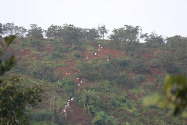Đoàn học sinh khoảng 30 em đang leo núi từ bản Đoàn Kết sang bản Tân Lập. Xuất hành từ sáng sớm, những học sinh này rủ nhau đi thành từ nhóm nhỏ. Nhìn từ quả đồi bên này, các em chỉ như những đốm nhỏ di động trên quả đồi dựng đứng