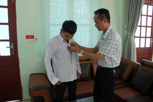 Thầy Nguyễn Văn Quang trao tặng em Duy áo đồng phục của nhà trường