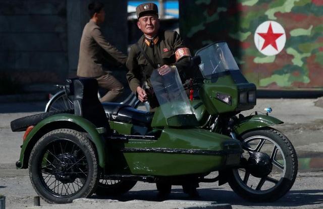 Một binh sĩ Triều Tiên đứng cạnh chiếc xe của mình.