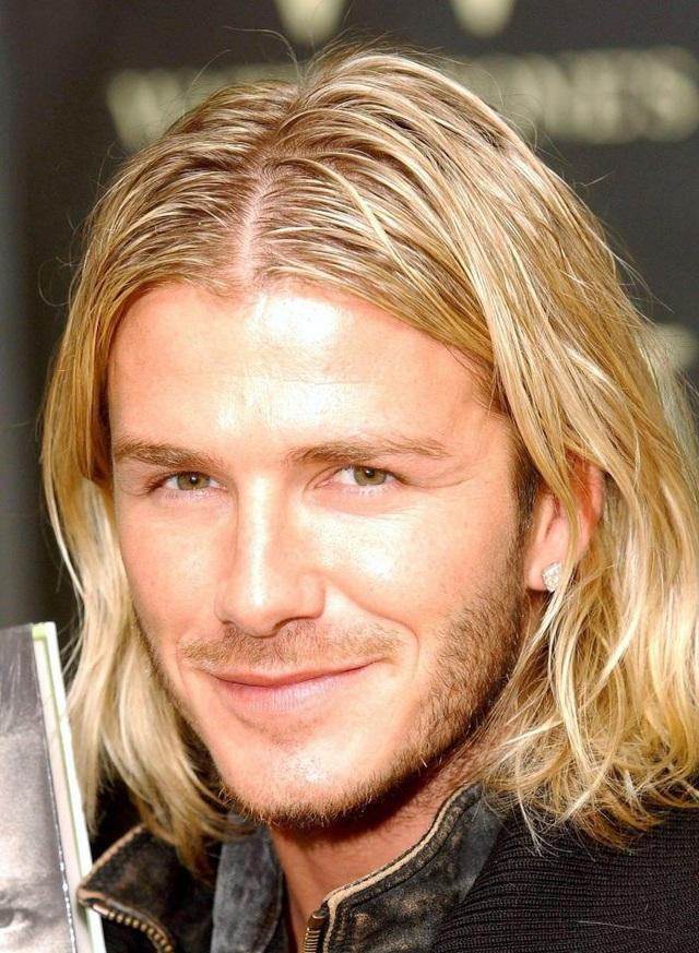 Beckham hoài cổ với mái tóc dài vàng óng bồng bềnh, chẻ ngôi giữa.