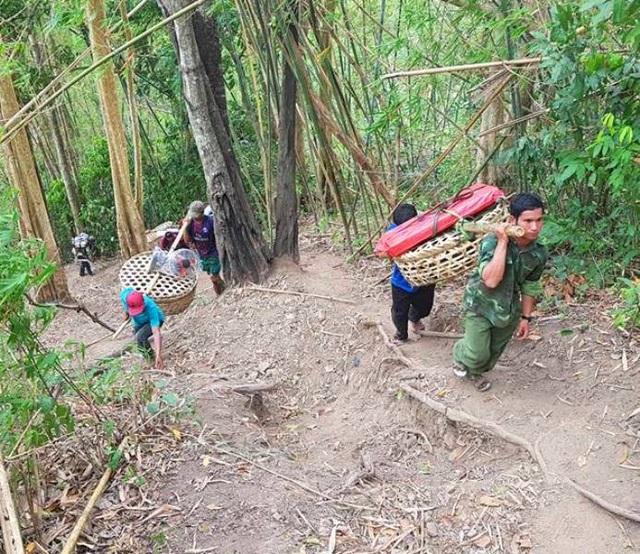 Các đoàn viên thanh niên và thanh niên trong làng O2 khiêng thiết bị điện mặt trời lên lắp cho người dân.