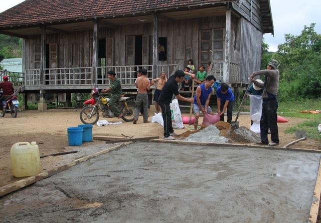 Đoàn viên thanh niên, thanh niên trong làng cõng từng bao xi măng để làm sân chơi cho thiếu nhi trong làng.