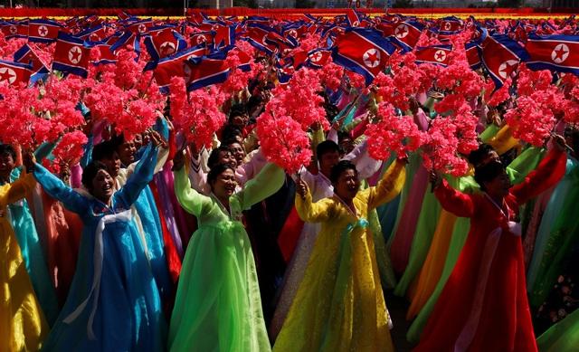 Không chỉ các binh sĩ tham gia lễ duyệt binh, lực lượng dân sự đại diện cho các nhóm ngành nghề khác nhau cũng cầm cờ, hoa, biểu ngữ diễu hành tại quảng trường Kim Nhật Thành. (Ảnh: Reuters)