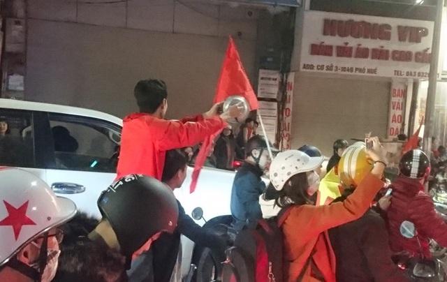 Thanh niên áo đỏ mang hai vung xoong mang ra khuấy động đám đông.