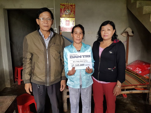 Đại diện lãnh đạo phường Điện An trao quà của bạn đọc Dân trí đến bà Phượng