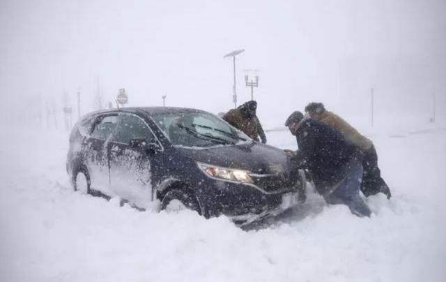 """Theo CBS, ít nhất 22 người đã thiệt mạng tại các bang ở Mỹ khi """"bom bão tuyết"""" lịch sử đổ bộ vào khu vực đông bắc nước này trong những ngày vừa qua. Trong ảnh: Những người đàn ông tìm cách giúp một người đi xe máy bị mắc kẹt trong tuyết ở bang New Jersey hôm 4/1. (Ảnh: AP)"""