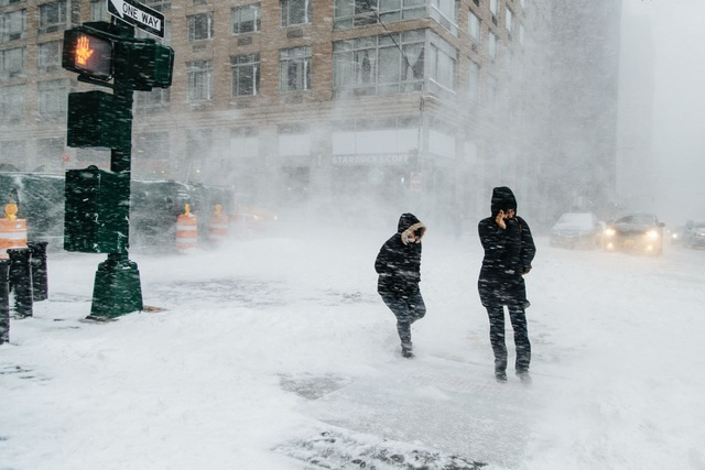"""""""Bom bão tuyết"""" khiến nhiều khu vực ở thành phố New York chìm trong khối tuyết dày, trong khi tại New England, ước tính cứ một giờ tuyết sẽ dày thêm 8 cm. Trong ảnh: Người đi bộ """"chống chọi"""" với gió tuyết để qua đường ở New York. (Ảnh: EPA)"""