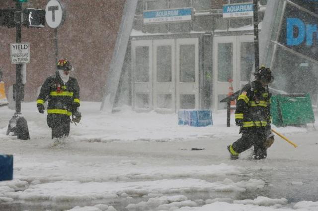 Hiện tượng tuyết rơi dày đã ảnh hưởng tới cuộc sống của hàng triệu người dân Mỹ. Các nhà chức trách và người dân ở khu vực bờ Đông nước Mỹ đang nỗ lực dọn tuyết để mở đường cho xe đi lại. Trong ảnh: Lính cứu hỏa bước qua con đường ngập trong nước và tuyết ở Boston. (Ảnh: Reuters)