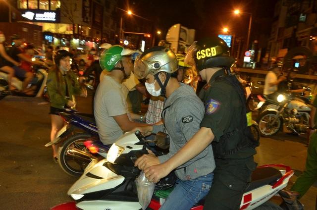 Nhiều người quá khích bị cảnh sát khống chế đưa về trụ sở để lập biên bản, tạm giữ xe