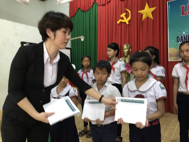 Bà Lục Quế Trang, trợ lý tổng giám đốc Cty Grobest VN, trao học hổng cho học sinh.