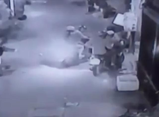 2 thanh niên đi xe máy (góc phải) giả vờ mua hàng để dàn cảnh cướp xe của đôi nam nữ phía bên trái hình.