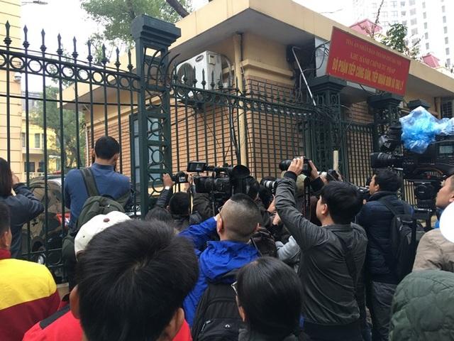 Các phóng viên đang đứng ngoài hàng rào của Toà để săn ảnh của các bị cáo.