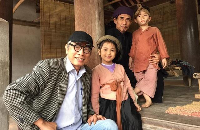 Đạo diễn Phạm Đông Hồng với diễn viên Phú Đôn cùng các diễn viên nhí trên phim trường Chôn nhời.