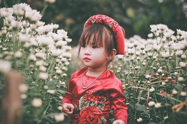 Khoảnh khắc ngọt ngào, dễ thương của bé gái 3 tuổi giữa sắc hoa tươi thắm.