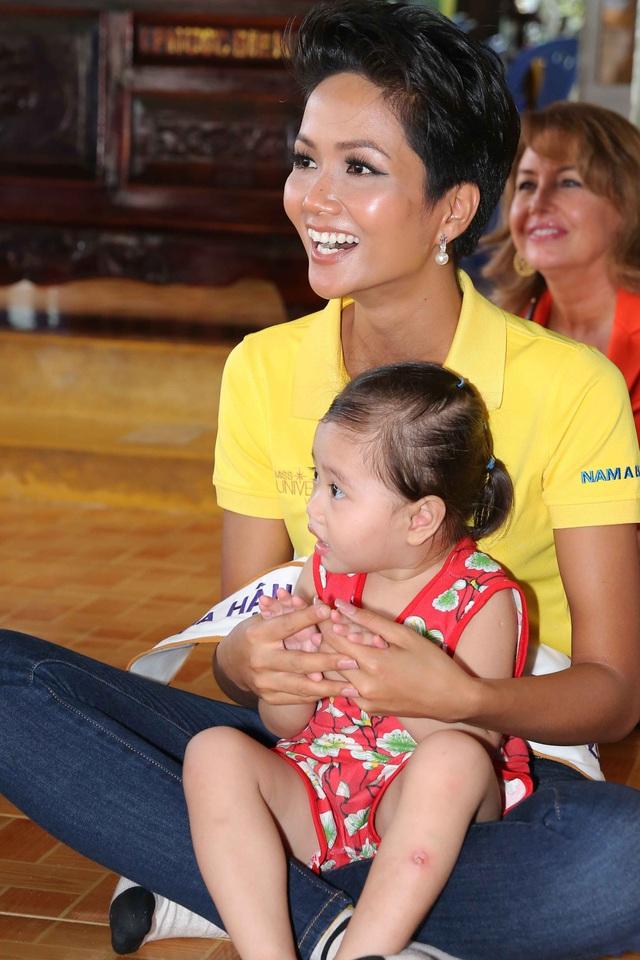 Không trang phục lộng lẫy như đêm chung kết, Hoa hậu H''hen Niê đầy giản dị trong trang phục áo thun, thân thiện chơi đùa cùng các em nhỏ.