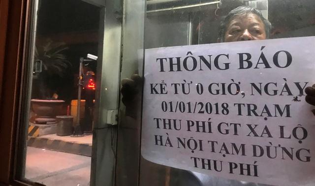 Nhân viên trạm thu phí XLHN dán thông báo việc tạm dừng thu phí.