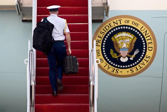 Một sĩ quan Thủy quân lục chiến Mỹ mang theo chiếc vali hạt nhân lên chuyên cơ Không lực Một của Tổng thống Mỹ. (Ảnh: Reuters)