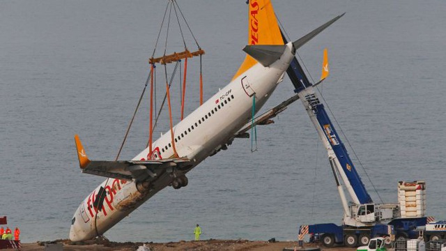 Chiếc máy bay gặp nạn được kéo lên bằng một cần cẩu lớn. (Ảnh: ABC News)