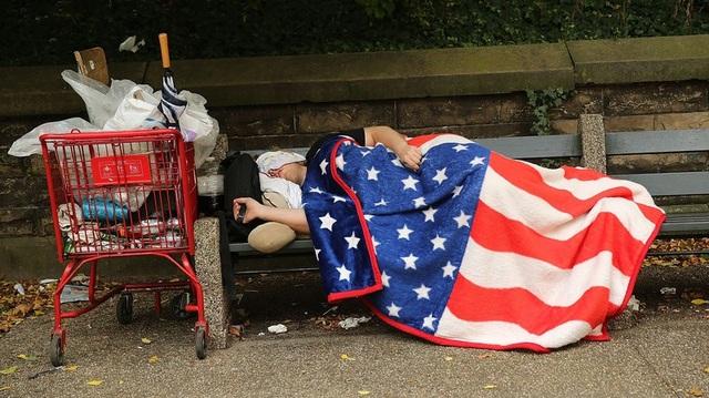 Một người vô gia cư ngủ trên ghế tại New York (Ảnh: Getty)