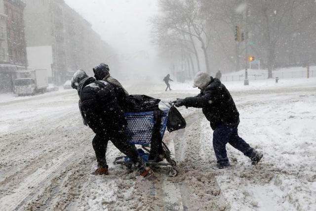 Nhiệt độ tại nhiều bang giảm xuống 20-30 độ so với mức bình thường, thậm chí tại những nơi gió thổi mạnh, nhiệt độ có thể xuống tới -23 độ C. Trong ảnh: Những người dân vất vả kéo xe chở đồ qua còn đường phủ đầy tuyết ở New York (Ảnh: Reuters)