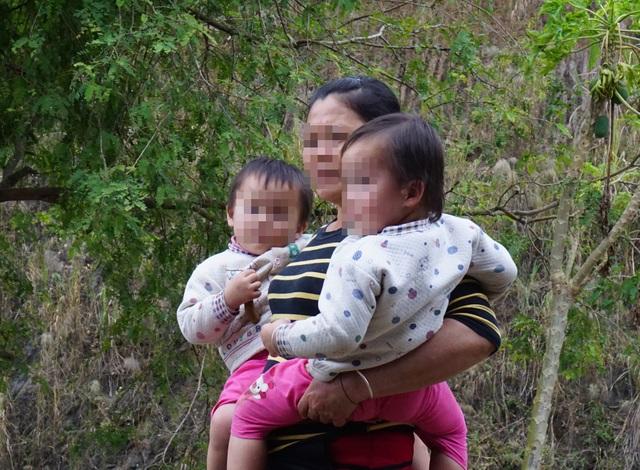 Bà Lô Thị K. 2 tay bế 2 đứa cháu ngoại được con gái đưa từ Trung Quốc về