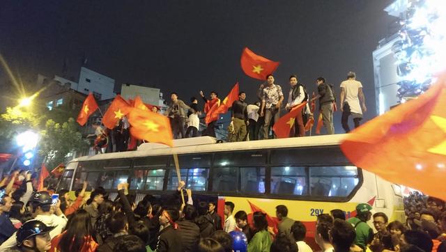 Xe buýt bị mắc kẹt giữa dòng người đã trở thành sân khấu bất đắc dĩ cho nhiều người đứng phất cờ...