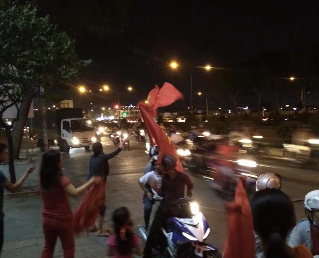 Trên hè phố ở các trục đường Trường Chinh, Cộng Hoà (TPHCM) nhiều người dân ra trước cửa nhà cầm cờ phấn thể hiện sự phấn khích, vui sướng trước chiến thắng của U23 VN