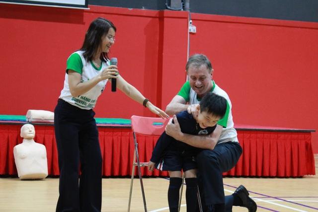 Thầy Tony Coffey và cô Trang Jena Nguyễn thực hành mẫu cách sơ cứu nạn nhân bị hóc thức ăn. (Ảnh: Ngọc Trang)